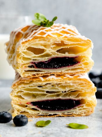 These Homemade Jam Filled Toaster Strudels are like mini flaky pies filled with homemade blackberry jam and topped with sweet vanilla glaze. #puffpastry #toasterstrudel #olgainthekitchen #pepperidgefarm #pie #pastry #jam #dessert #breakfast