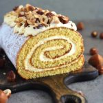 The BEST fluffy and moist Honey Cake Roll that is easier than any cake, filled with scrumptious sweetened condensed milk frosting and topped with hazelnuts for a hint of nutty flavor. This dessert is a family staple and such a crowd-pleaser! olgainthekitchen.com