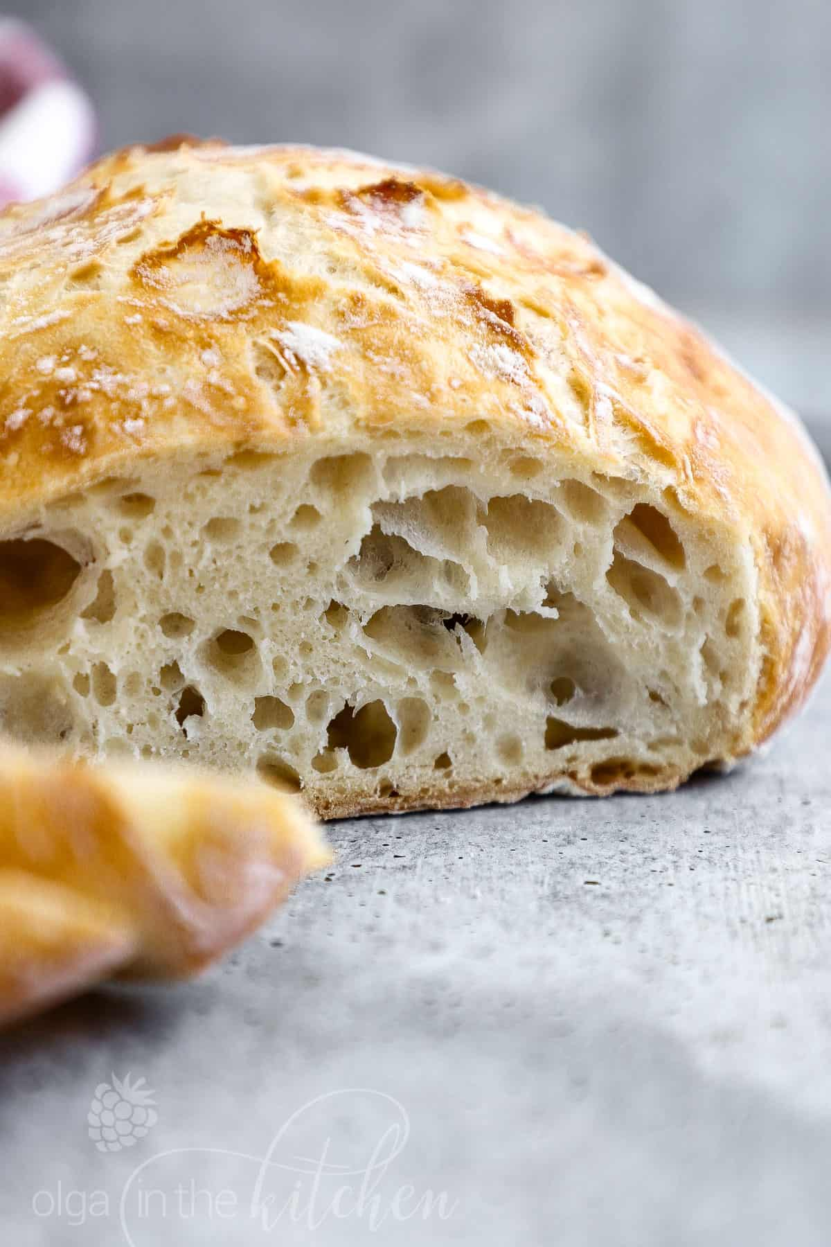This easy No-Knead Bread loaf has a deliciously crisp crust and a soft spongy center. It's the perfect blend of soft and chewy. With only 4 ingredients (flour, salt, yeast and water), you can make a bakery-quality, scrumptious loaf of homemade bread. #nokneadbread #bread #olgainthekitchen #easyrecipe #recipes #rusticbread