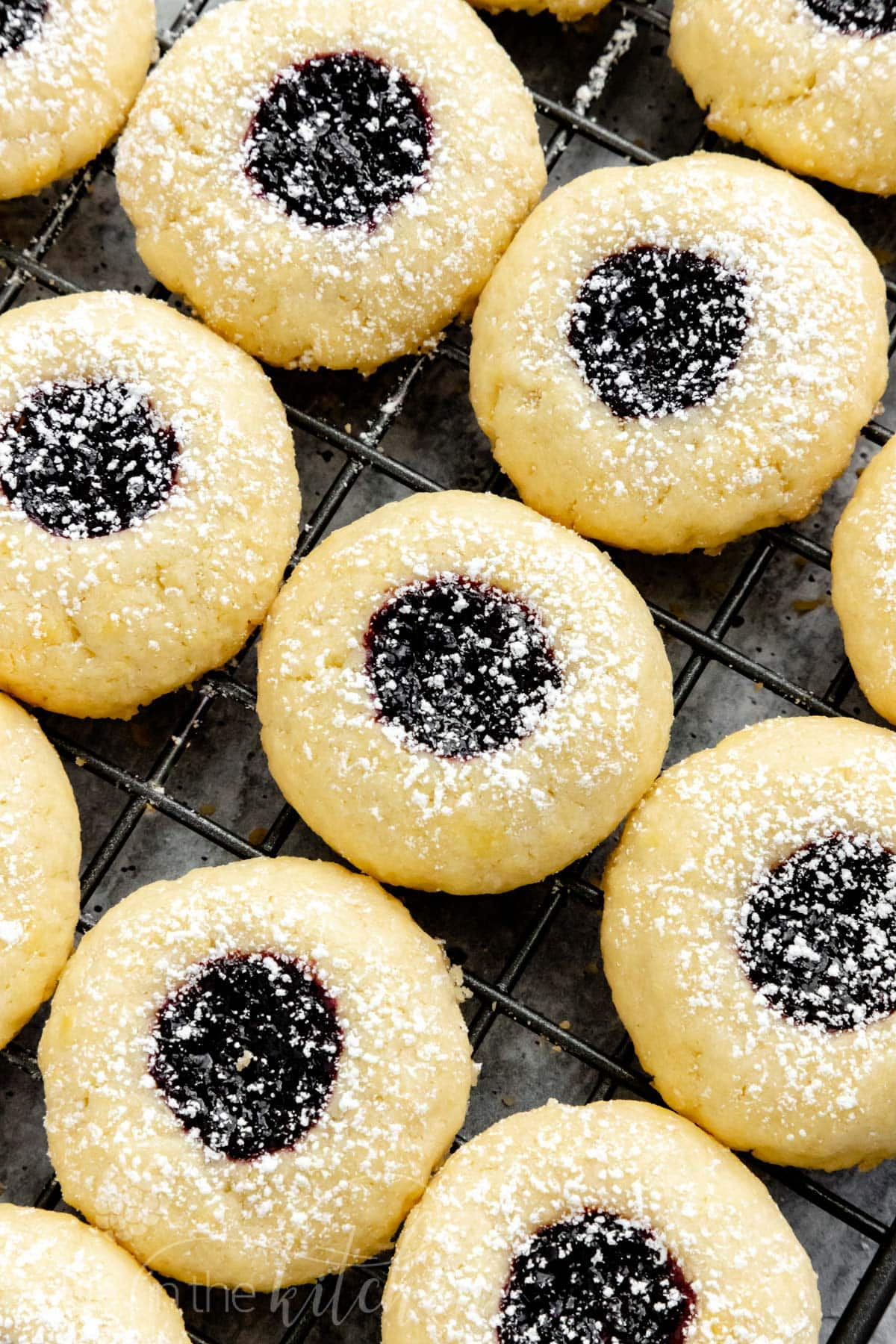 These Jam-Filled Thumbprint Cookies combine soft butter cookies and a sweet jam filling. Use your favorite jelly flavor like blackberry, strawberry, raspberry or other favorites. Add a light dust of powdered sugar for extra flair and these cookies bound to disappear off cookie platters fast. #thumbprintcookies #cookies #jamcookies #olgainthekitchen #dessert #homemade