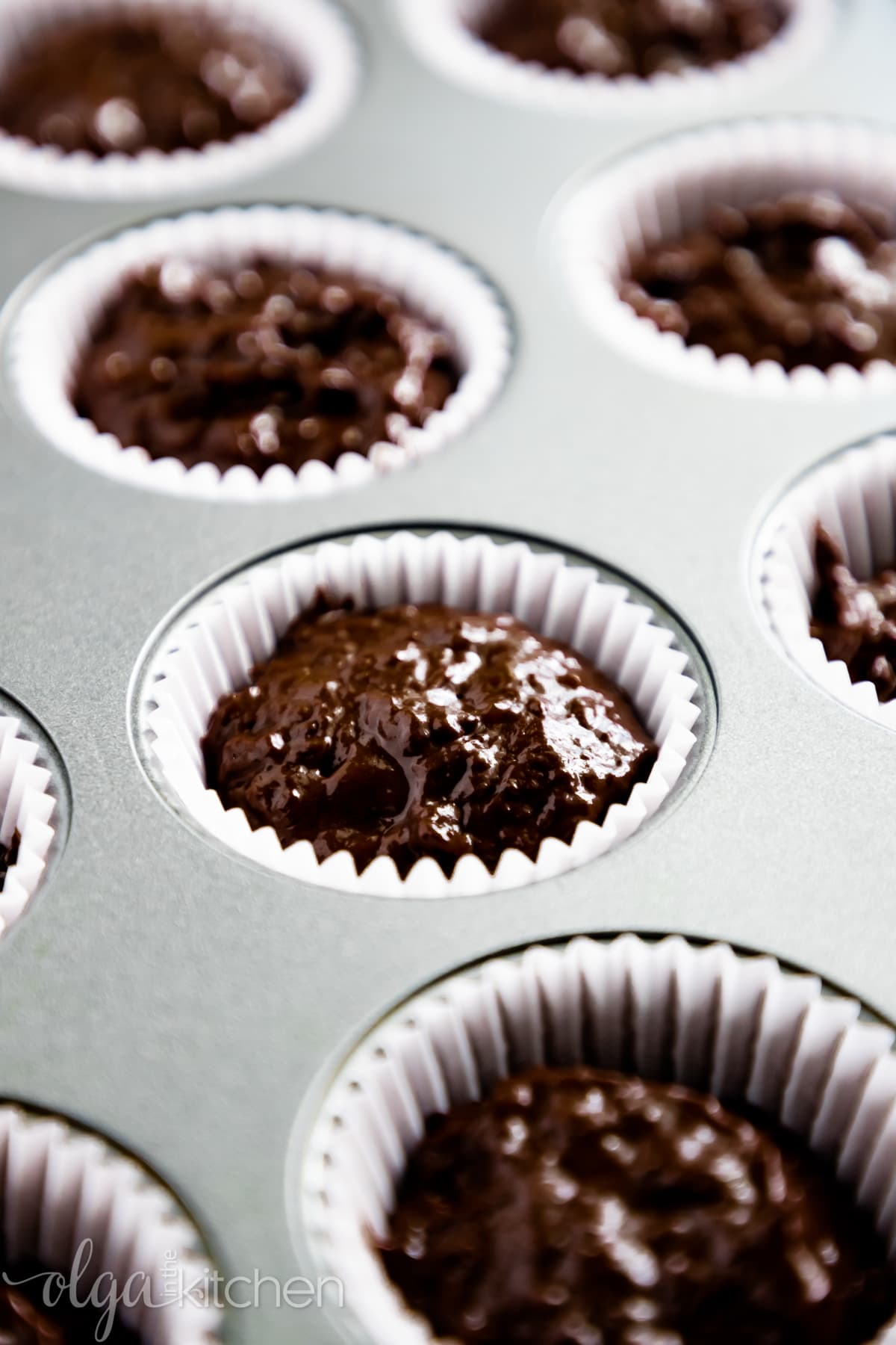 Fill muffin liners with batter for Chocolate Banana Muffins.